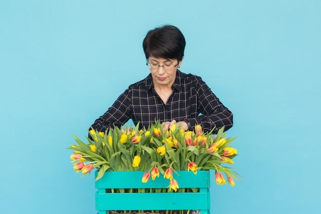 Charmante brunette vrouwelijke bloemist sorteert tulpen in de doos