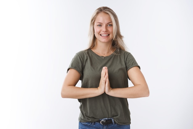 Charmante charismatische ontspannen europese blonde vrouw die handpalmen tegen elkaar drukt over het lichaam in namaste gebaar glimlachend in het algemeen vredig en kalm voelen na meditatie yoga beoefenen over witte muur