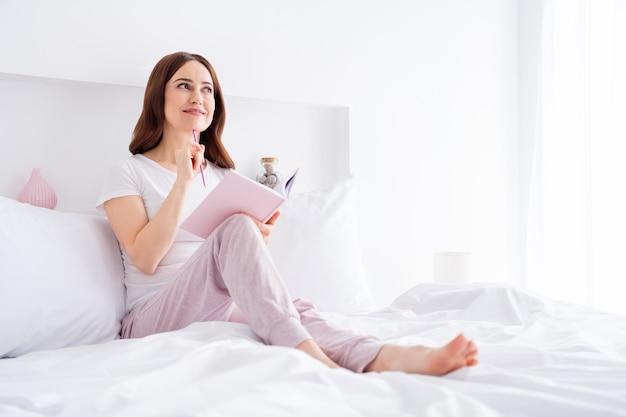 Charmante creatieve meisje zittend in bed een verhaal te creëren
