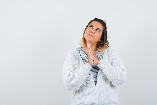 Charmante dame die gevouwen handen toont in een biddend gebaar in t-shirt, vest en er hoopvol uitziet