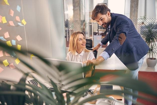 Charmante dame die naar collega kijkt en glimlacht terwijl ze aan tafel zit met de computer op kantoor