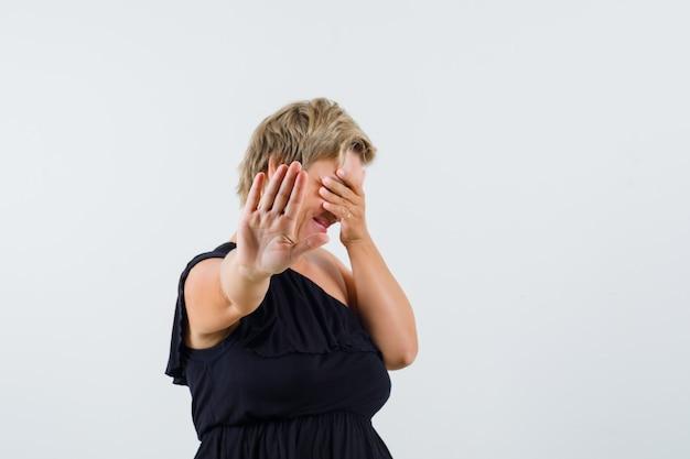 Charmante dame die stopgebaar in zwarte blouse toont en terughoudend kijkt