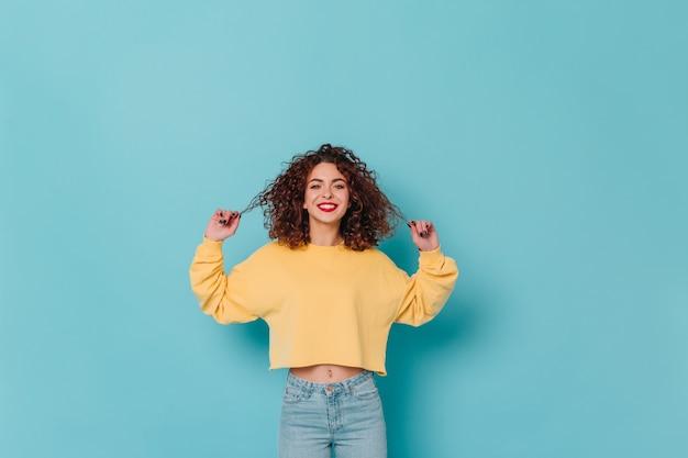 Charmante dame in gele trui en skinny jeans glimlacht en raakt haar donkere krullende haar aan tegen de blauwe ruimte.