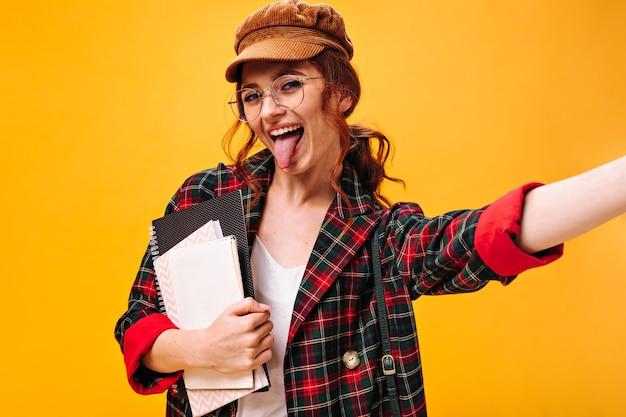Charmante dame in geruite outfit demonstreert haar tong, houdt notitieboekjes vast en maakt selfie