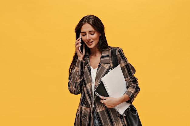 Charmante dame in oversized jas praat aan de telefoon