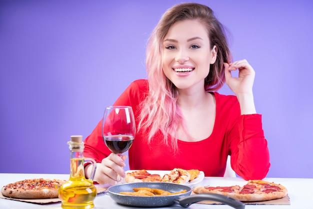 Charmante dame in rode blousezitting bij de lijst met glas wijn