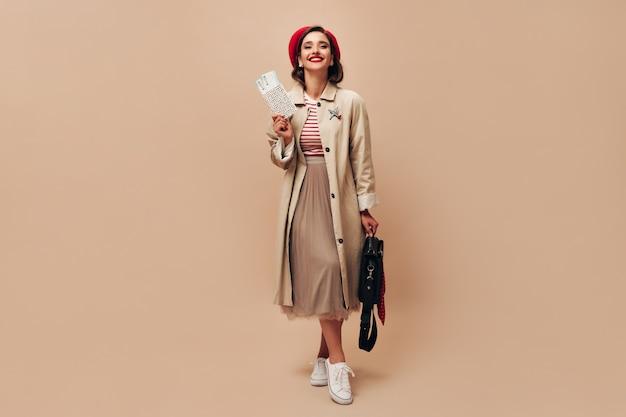 Charmante dame in rode hoed en beige loopgraaf houdt kaartjes. mooie vrouw in stijlvolle lange jas en in gestreepte trui met zwarte tas poseren.