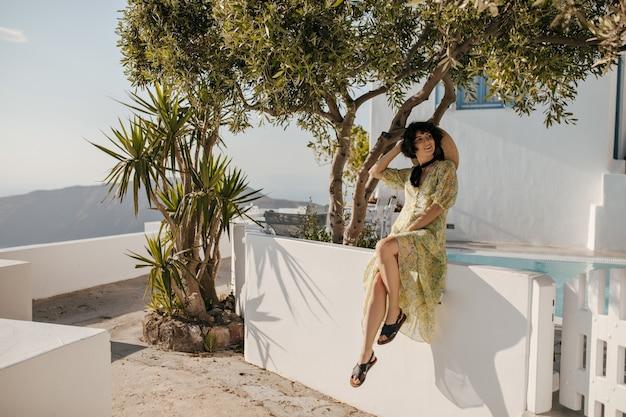 Charmante dame in schipper, groene jurk poseert in een goed humeur in de buurt van olijfboom, zwembad en wit gebouw