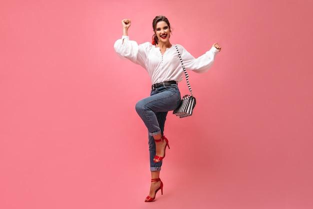 Charmante dame in spijkerbroek dansen op roze achtergrond. leuk krullend meisje in modieuze kleding en rode hoge hakken lacht op geïsoleerde achtergrond.