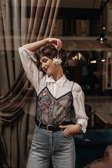 Charmante dame in wit overhemd met zwarte kant en spijkerbroek glimlachend in café. vrouw met heldere lippen en kort haar houdt bloem binnen.