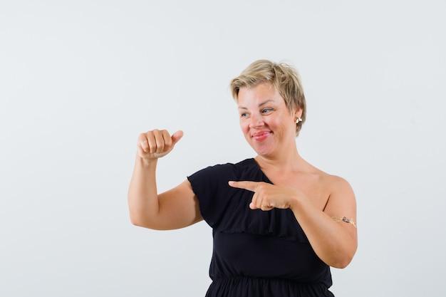 Charmante dame in zwarte blouse die iets vasthoudt terwijl ze erop wijst
