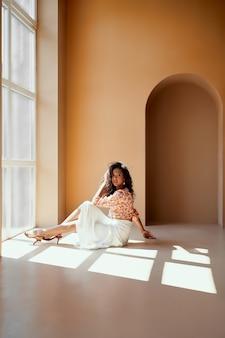 Charmante dame met donker haar zittend op de vloer bij het raam