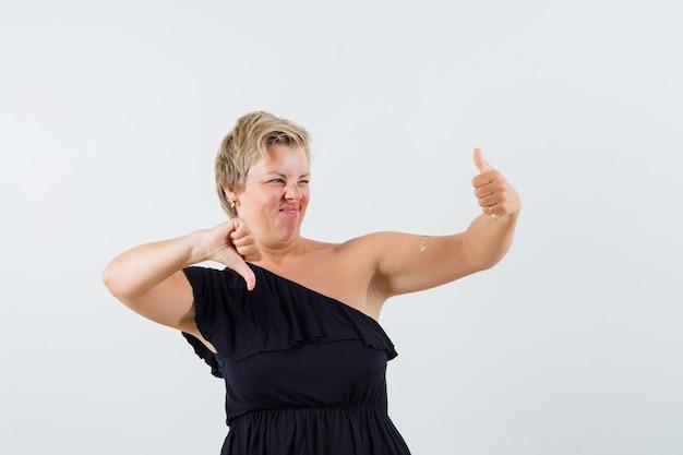 Charmante dame met duim op en neer in zwarte blouse en aarzelend op zoek. vooraanzicht.