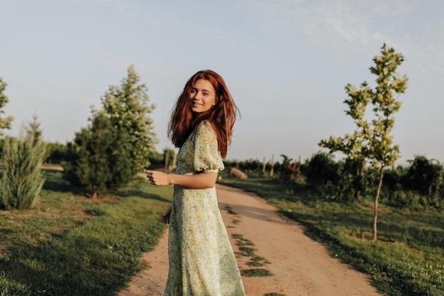 Charmante dame met foxy kapsel in modieuze gele en groene jurk die naar voren kijkt en lacht op de muur van de weg