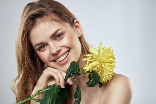 Charmante dame met gele bloem op een licht bijgesneden uitzicht.