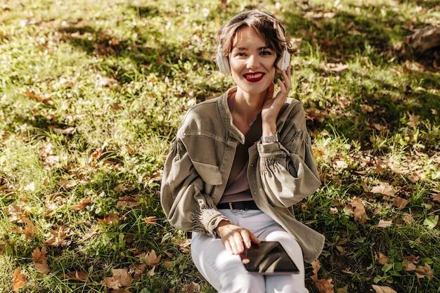 Charmante dame met kort haar in olijfjasje en broek zit op gras en houdt smartphone buitenshuis. vrouw in hoofdtelefoons glimlacht buiten.