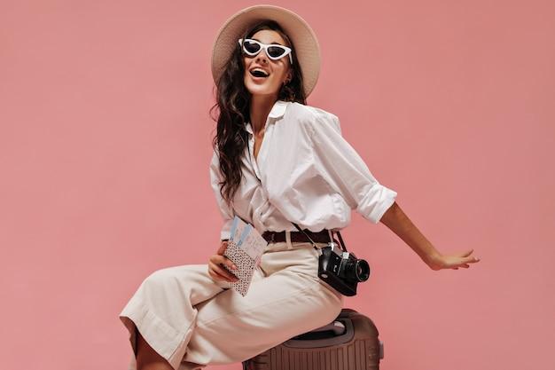 Charmante dame met lang krullend haar in coole zonnebrillen, moderne kleding en lichte hoed poseren met camera en kaartjes op roze muur