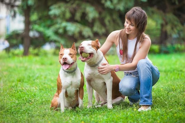 Charmante dame poseren met honden buitenshuis.