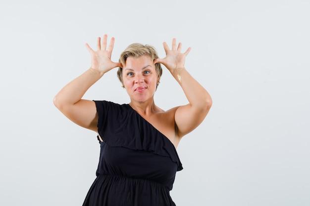 Charmante dame toont stierhoorn boven haar hoofd in zwarte blouse en kijkt speels