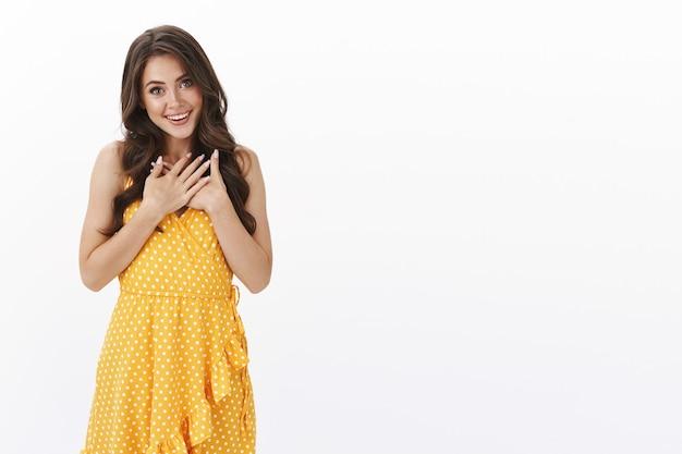 Charmante dankbare glamour jonge vrouw in gele jurk hand in hand, zuchtend dankbaar, tevreden glimlachen, ontroerend hartverwarmend geschenk ontvangen, inspanning waarderen, witte muur verrast staan