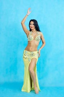 Charmante danseres voert oosterse buikdans op een blauwe achtergrond uit.