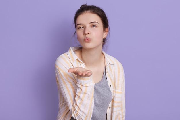 Charmante donkerbruine jonge vrouw die vrijetijdskleding dragen die luchtkus tonen, houdt lippen rond