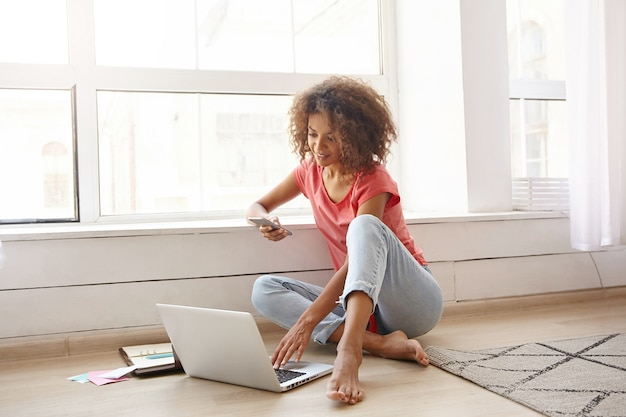 Charmante donkere gekrulde vrouw zitten in de buurt van groot raam, smartphone in de hand houden en e-mails controleren op laptop, vrijetijdskleding dragen