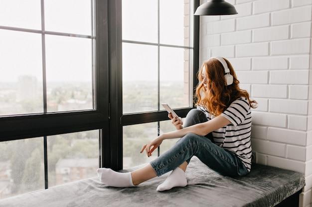 Charmante donkerharige meisje, zittend op de vensterbank met telefoon. lieve gemberdame in koptelefoon sms-bericht. Gratis Foto