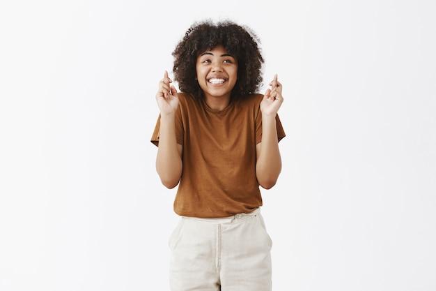 Charmante dromerige optimistische donkere vrouw in bruin t-shirt schouderophalend van ongeduld glimlachend breed gekruiste vingers voor geluk, wachtend op droom die uitkomt over grijze muur