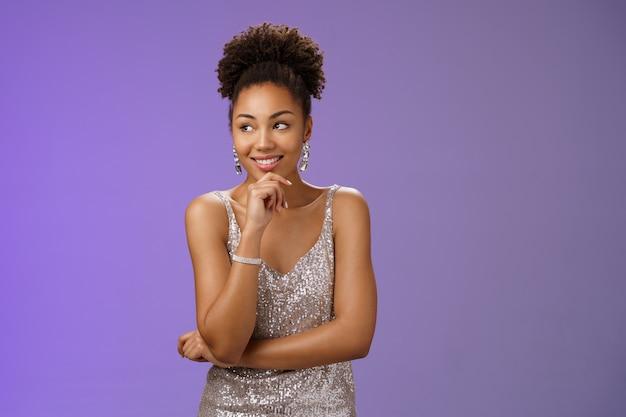 Charmante elegante afro-amerikaanse vrouw, gekleed in zilveren glanzende luxe jurk glimlachend opgetogen zelfverzekerde touch kin doordachte ontwerper genieten van inspiratie modeweek, blauwe achtergrond.