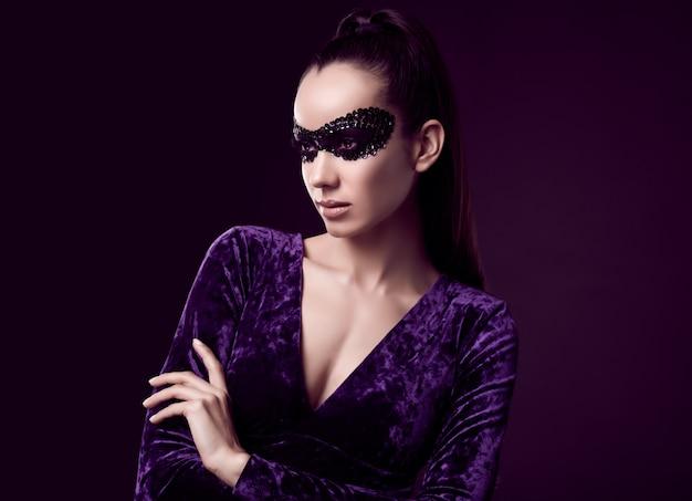 Charmante elegante brunette vrouw in paarse jurk en pailletten masker