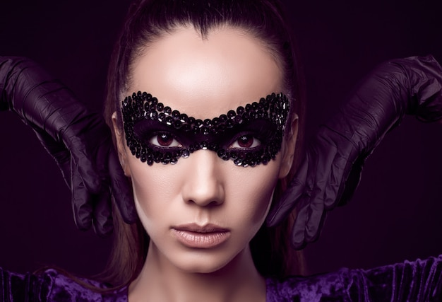 Charmante elegante brunette vrouw in pailletten masker en handschoenen