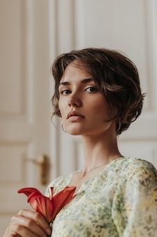 Charmante elegante jonge gebruinde vrouw met bruine ogen in gebloemde jurk houdt rode bloem vast en poseert in de buurt van houten witte deuren