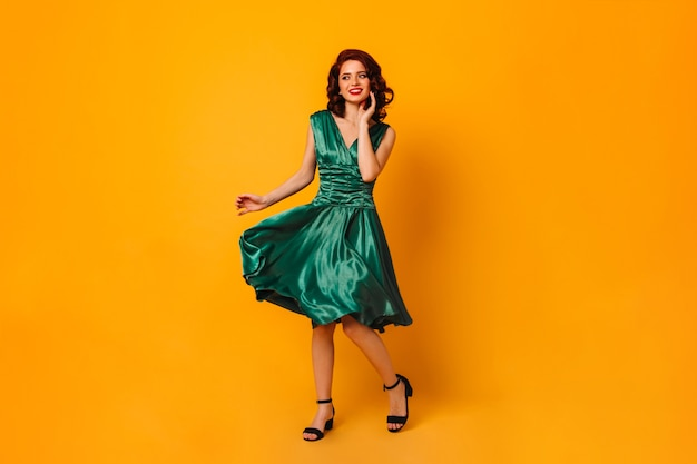 Charmante en vrouw in groene kleding die weg glimlacht kijkt. volle lengte weergave van prachtig krullend meisje dansen op gele ruimte.
