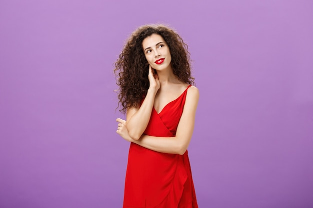 Charmante en zachte elegante vrouw met krullend kapsel in stijlvolle rode avondjurk kantelend hoofd nek aanraken en staren naar de rechter bovenhoek tedere, dagdromen poseren over paarse achtergrond.
