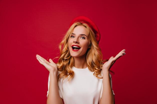 Charmante franse jonge vrouw genieten van fotoshoot. binnen schot van vrolijk wit meisje in franse baret.