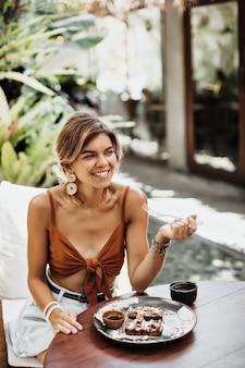 Charmante gebruinde vrouw in bruine beha en spijkerrok glimlacht en eet wafel met ahornsiroop