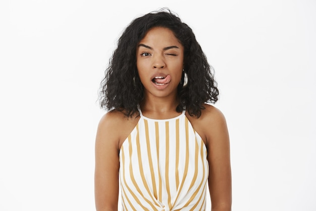 Charmante, gedurfde en sensuele flirterige vrouw met een donkere huidskleur in een gestreepte gele top met een knipoog en een tong uitsteekt
