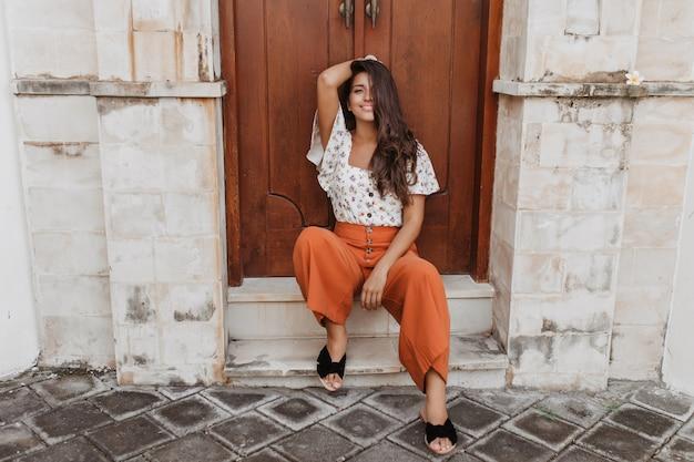 Charmante gekrulde brunette vrouw in culottes en witte blouse zit op drempel van huis met houten deur