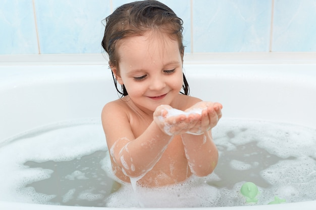 Charmante gelukkige baby die bad neemt, dat gelukkig met schuimbellen speelt.