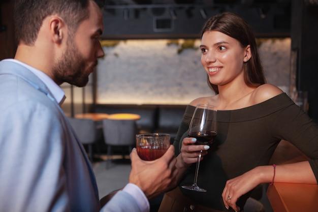 Charmante gelukkige jonge vrouw cocktails drinken met haar vriend aan de bar