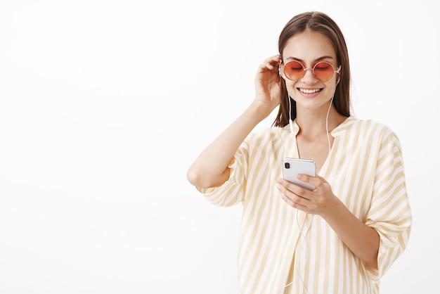 Charmante, gezellige en modieuze jonge europese vrouwelijke model in gestreepte gele blouse en zonnebril zetten haarlok achter het oor staren naar smartphonescherm liedje plukken om te luisteren in oortelefoons