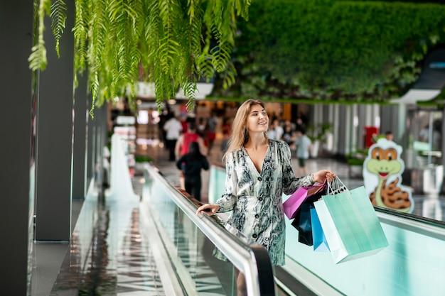 Charmante glimlachende dame geïnspireerd door winkelen om de roltrap in het winkelcentrum te berijden. grote aankopen. uitverkoop.