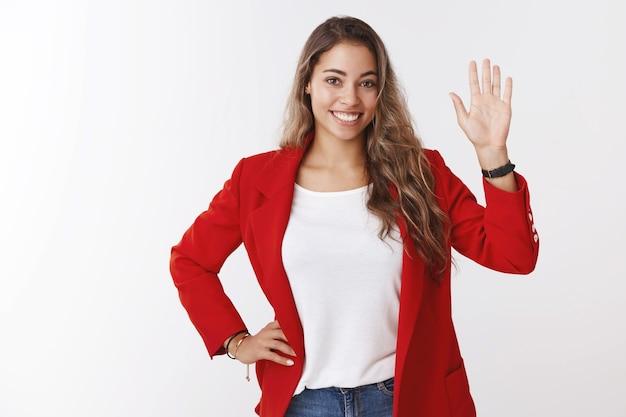 Charmante glimlachende gelukkig vriendelijk ogende blanke zakenvrouw met krullend haar die nieuwe werknemers verwelkomt die grijnzend aangenaam zwaaien met opgeheven hand hallo, groetend gebaar, gedag zeggen, witte muur