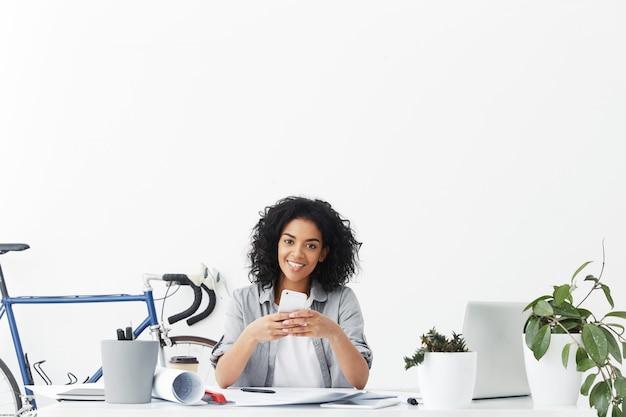 Charmante glimlachende jonge donkere vrouwelijke ontwerper die taxi aanvraagt met behulp van de online app