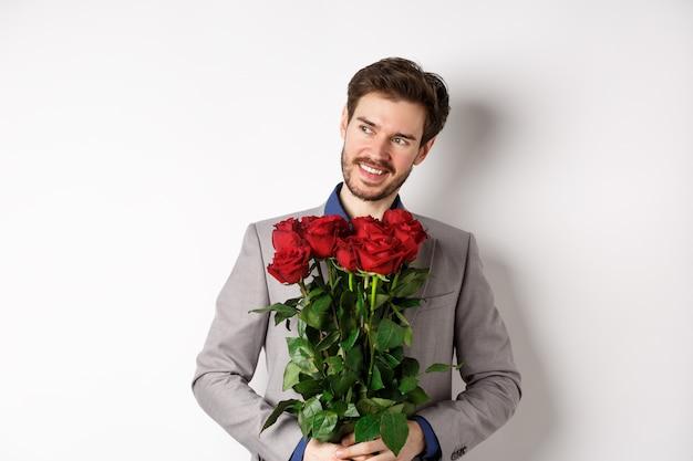 Charmante glimlachende man die op romantische date gaat, pak draagt, boeket rozen vasthoudt en naar links kijkt, staande op valentijnsdag met cadeau op witte achtergrond.