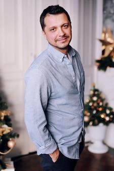 Charmante glimlachende man naast een kerstboom