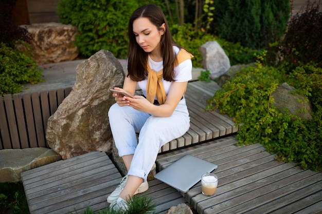 Charmante gratis jonge vrouw in casual look is koffie drinken zittend in een zomerpark.