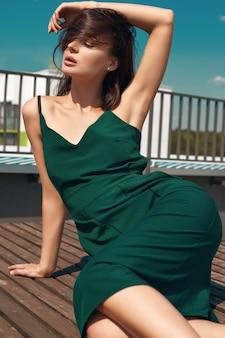 Charmante heldere brunette in een smaragdgroene jurk