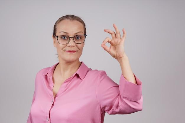 Charmante hogere bedrijfsvrouw die glazen, roze blouse draagt, die goed gebaar toont. geïsoleerde foto op grijze achtergrond met kopie ruimte.